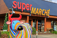 A painted cow outside a supermarket in the small village at the entrance to Mont San Michel in Normandy, France