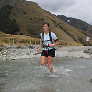 Runner Gabbie Ernst crosses Moke Creek on the Ben Lomond High Country Station during the Pure South Shotover Moonlight Mountain Marathon and trail runs. Moke Lake, Queenstown, New Zealand. 4th February 2012. Photo Tim Clayton