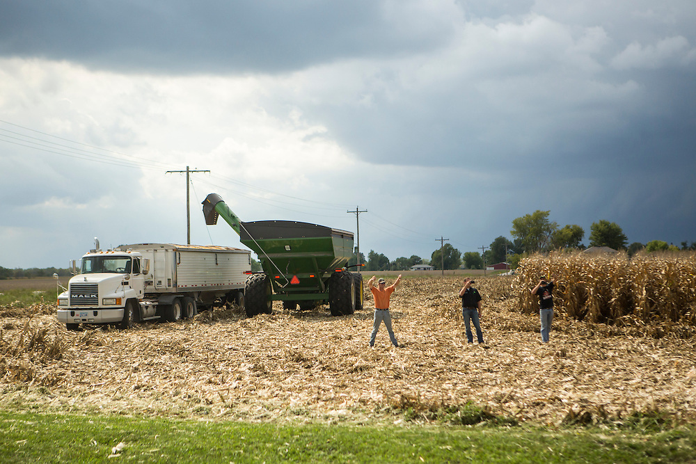 People standing in a field give a thumbs down as Vice President Joe Biden's motorcade passes by on the way to a campaign rally at the Port of Burlington during a two-day campaign swing through Iowa on Monday, September 17, 2012 in Burlington, IA.