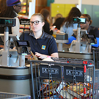Michealla Schallock, a chashier at ALDI, keeps her eye on her register as she checks out customers items during the ALDI grand opening on Wednesday morning in TUpelo.