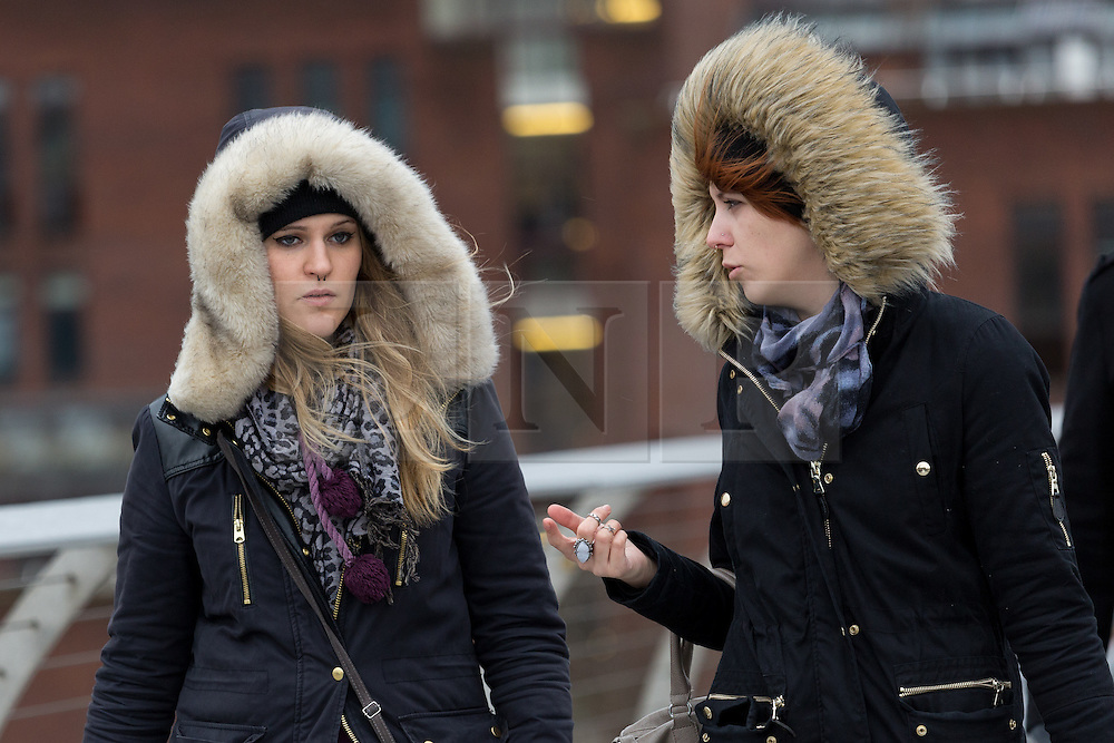 © Licensed to London News Pictures. 27/01/2016. London, UK. Two women walk across Millennium Bridge during wet and windy weather. Storm Jonas continues to bring rain and gales to the UK today.  Photo credit : Vickie Flores/LNP