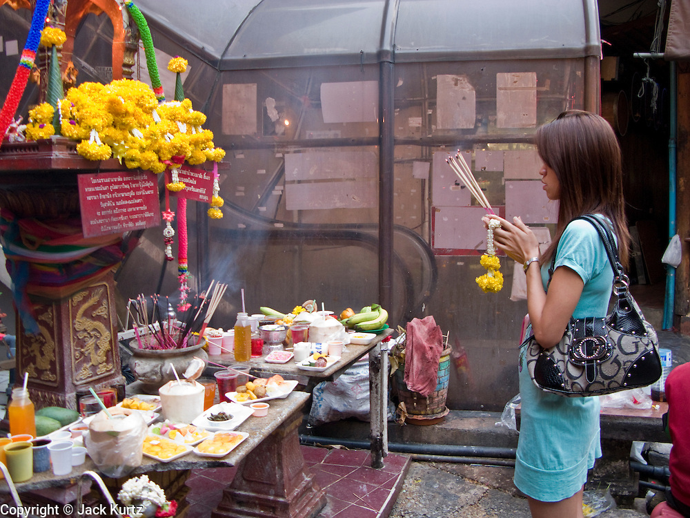 29 FEBRUARY 2008 -- BANGKOK, THAILAND:  A woman prays at a Buddhist shrine in the Nana Entertainment District, one of the adult entertainment red light districts in Bangkok, Thailand.   Photo by Jack Kurtz
