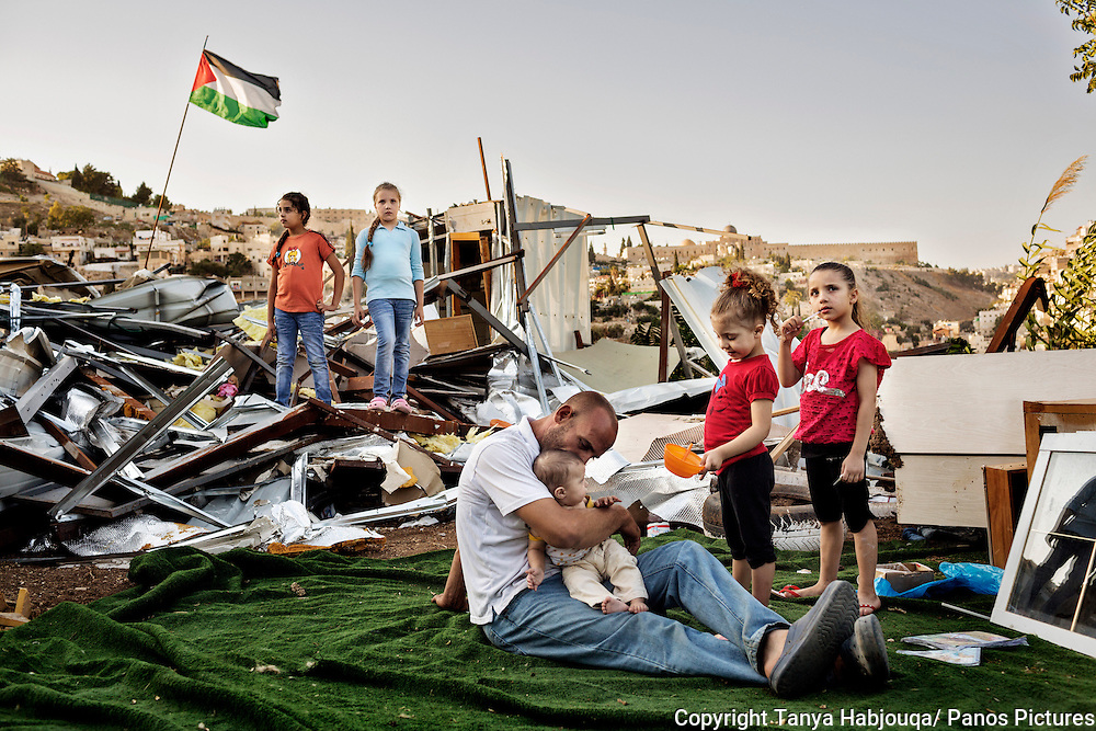 Khalid Zir and his five daughters take a break beside the ruins of their demolished home, in the East Jerusalem neighborhood of Silwan.