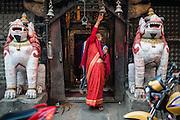 Woman ringing bell at hindu temple in Kathmandu (Nepal)