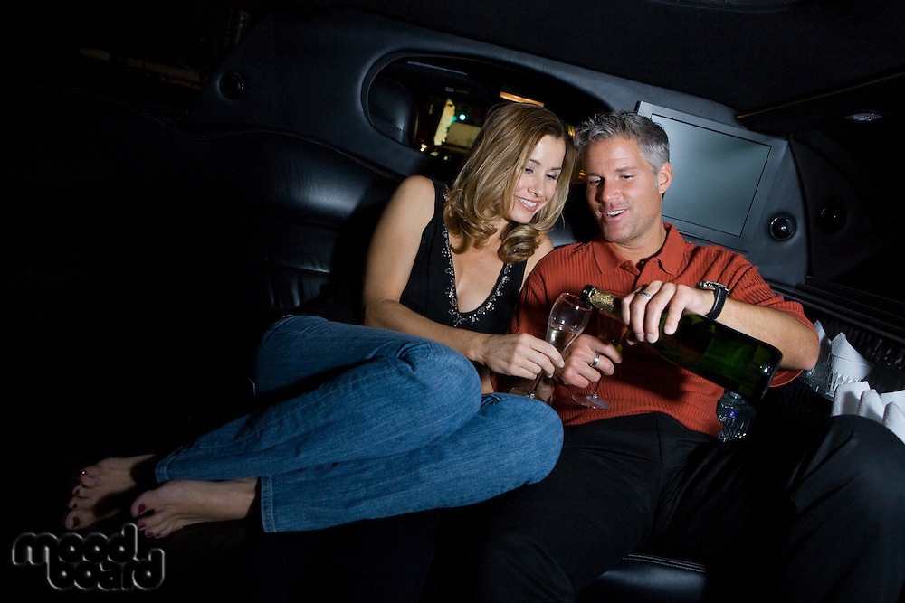 Mid-adult couple sitting on back seat of limousine and drinking champagne