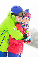 Happy loving man hugging woman in snow
