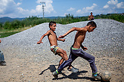 Teenagers playing football during a tropical day at the Roma settlement  in Moldava nad Bodvou. The city has roughly 11200 inhabitants, about 1980 (18%) of them have Roma ethnicity and around 800 are living at the segregated settlement 'Budulovska Street' (2014).