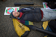A man staging a lie-down in front of a line of police officers at the North Gate of Her Majesty's Naval Base, Clyde, Faslane, Scotland, during a blockade by around 150 people protesting against the Trident nuclear missile system. The protestors managed to shut down the base, preventing workers, contractors and naval personnel from accessing the site. A decision was due to be made by the UK government in 2016 whether to replace the Trident submarine system.