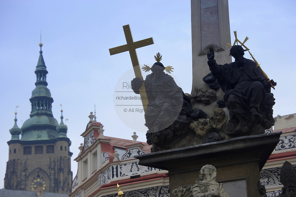 Detail of the St John the Baptist on the Plague Column  in Mala Strana square with Prague Castle in the distance in Prague, Czech Republic. The castle, first constructed in the 10th century is the seat of government in the Czech Republic.