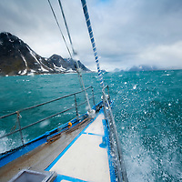 Norway, Svalbard, View through bow of expedition yacht SY Arctica motoring through rough seas on summer morning