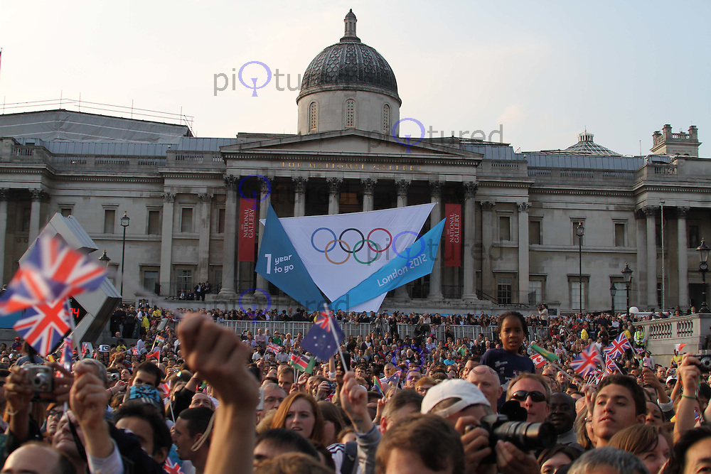 With one year to go until the Opening Ceremony of the London 2012 Olympic Games The President of the International OIympic Committee Jacques Rogge and the Mayor of London Boris Johnson both formally invited the athletes and the people of the world to the Games next summer. The design of the Olympic medals were also unveiled. Trafalgar Square, , London, UK, 27 July 2011:  Contact: Rich@Piqtured.com +44(0)7941 079620 (Picture by Richard Goldschmidt)