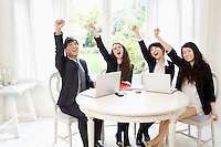 Successful businesspeople with hand raised