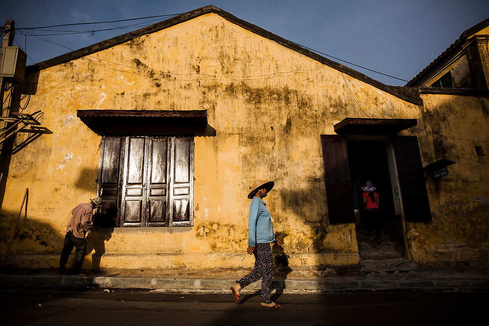 A local woman walks past an old building in downtown Hoi An, Vietnam. Hoi An is a UNESCO-recognized World Heritage Site, and a popular tourist destination in Vietnam.