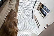 An ancient egyptian statue watches silently as the tourist walk by the British Museum entrance hall