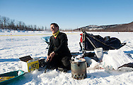Martin Buser talks with fans and volunteers as he readies food for his dogs in Iditarod on Thursday.