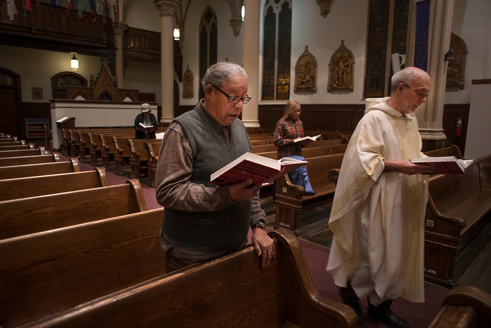 George Smith sings during a Mass celebrating the Solemnity of the Immaculate Conception in December presided over by Father Richard Zelik (right) at St Benedict the Moor Church in the Hill District.
