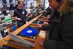 © Licensed to London News Pictures. 13/04/2019. LONDON, UK. Customers listen to LPs in Phonica Records. Analogue music fans visit independent record shops in Soho to celebrate vinyl music on the 12th Record Store Day.  Over 200 independent record shops across the UK come together annually to celebrate the unique culture of analogue music with special vinyl releases made exclusively for the day.  In 2018, sales of vinyl rose for the 11th consecutive year to 4.2 million units according to the British Phonographic Industry (BPI).  Photo credit: Stephen Chung/LNP