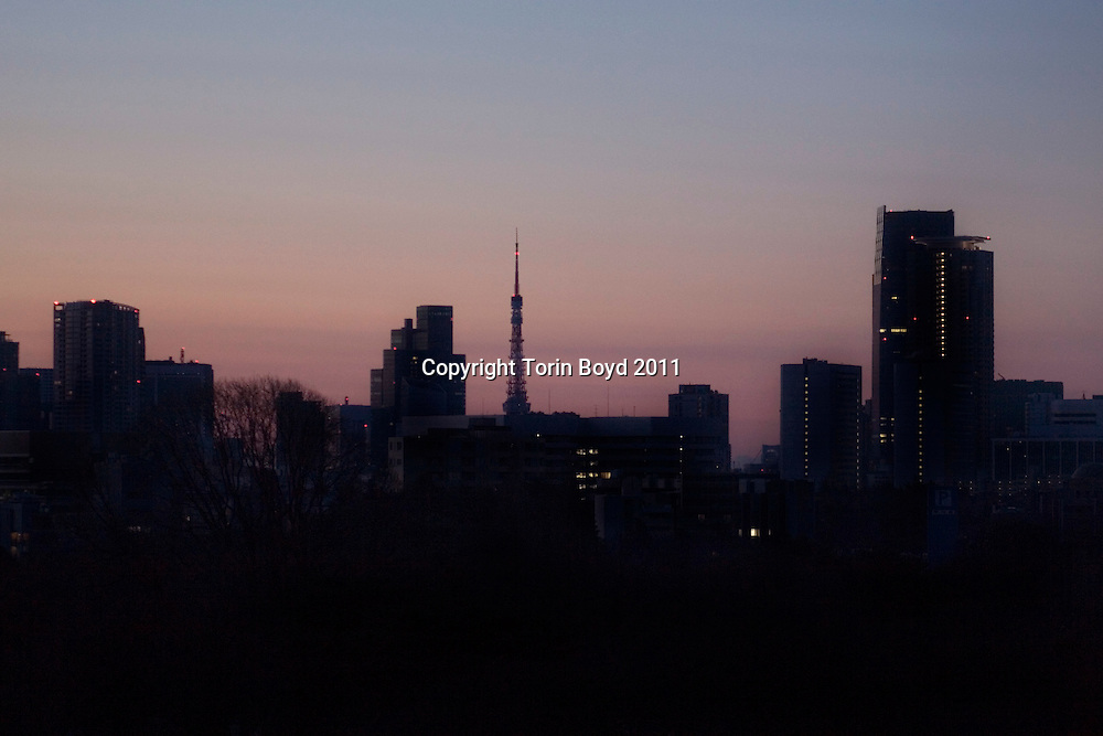 This view shows the brownout skyline of Tokyo looking east to the center of Tokyo and Tokyo Bay (Tokyo Tower center, Tokyo Midtown right). It was taken from the Shinjuku district at 5:40 am, on March 18, 2011 just before sunrise. The previous night, due to the severe power shortages caused by to checks and inspections of all nationwide nuclear power plants, much of the Tokyo/Kanto area was on a self imposed brownout. But around 7:00 p.m. it was announced that if Tokyoites did not practice self restraint in conserving electricity, the city would suffer a complete total blackout by midnight. That never happened though as all residents, businesses and transportation services drastically cut back. As a result, this was literally the darkest night in Tokyo in the past thirty years (not sure of blackout history prior to 1980 - check). This brownout was all a result of the massive March 11, 2011 earthquake measuring 9.0 mag. that struck Japan causing widespread catastrophe, and worse, severe damage to the Fukushima Daiichi nuclear power pant.