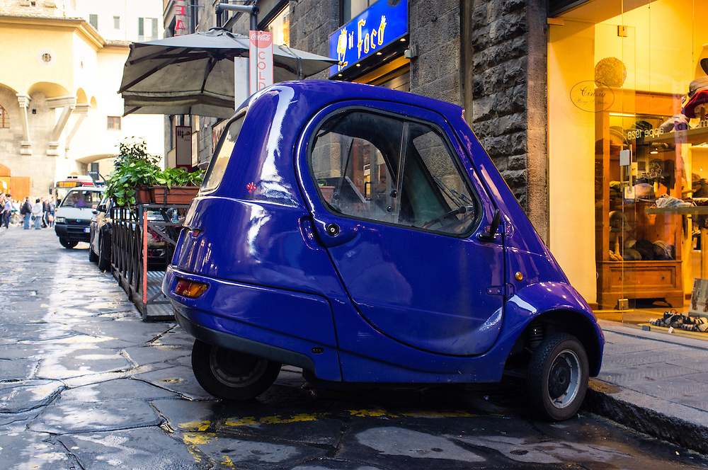 Small old Italian car parked in a side street in Florence, Italy