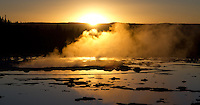 The autumn sun sets behind Great Fountain Geyser in Yellowstone National Park