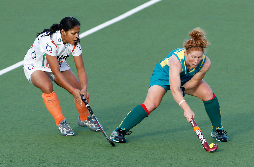 Australia's Georgia Nanscawen, right, looks to get past India's Deepika during their four nations hockey match at North Harbour Hockey Stadium, Auckland, New Zealand, Sunday, April 15, 2012. Credit:SNPA / Ben Campbell..