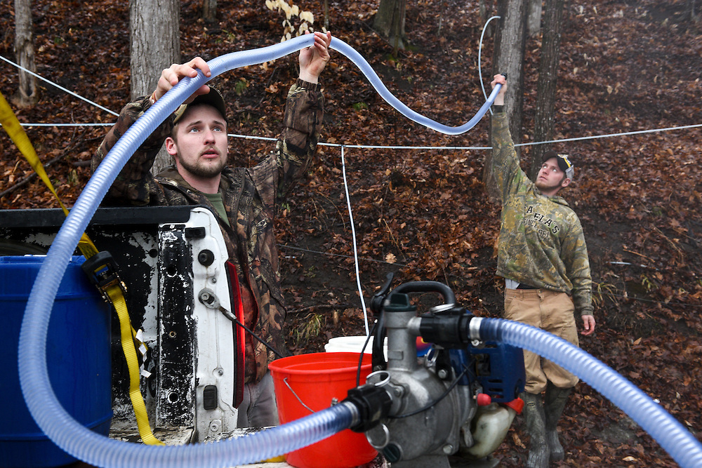 A.J. Potwin, of Sharon, left, and Scooter Cadwell, of Sharon, right, attempt to prime an uncooperative pump while collecting maple sap from about 150 taps for L.L. Potwin Services at their sugar bush in Quechee, Vt. Thursday, March 26, 2015. L.L Potwin also has about 1100 taps at a sugarbush in Sharon. (Valley News - James M. Patterson)<br />