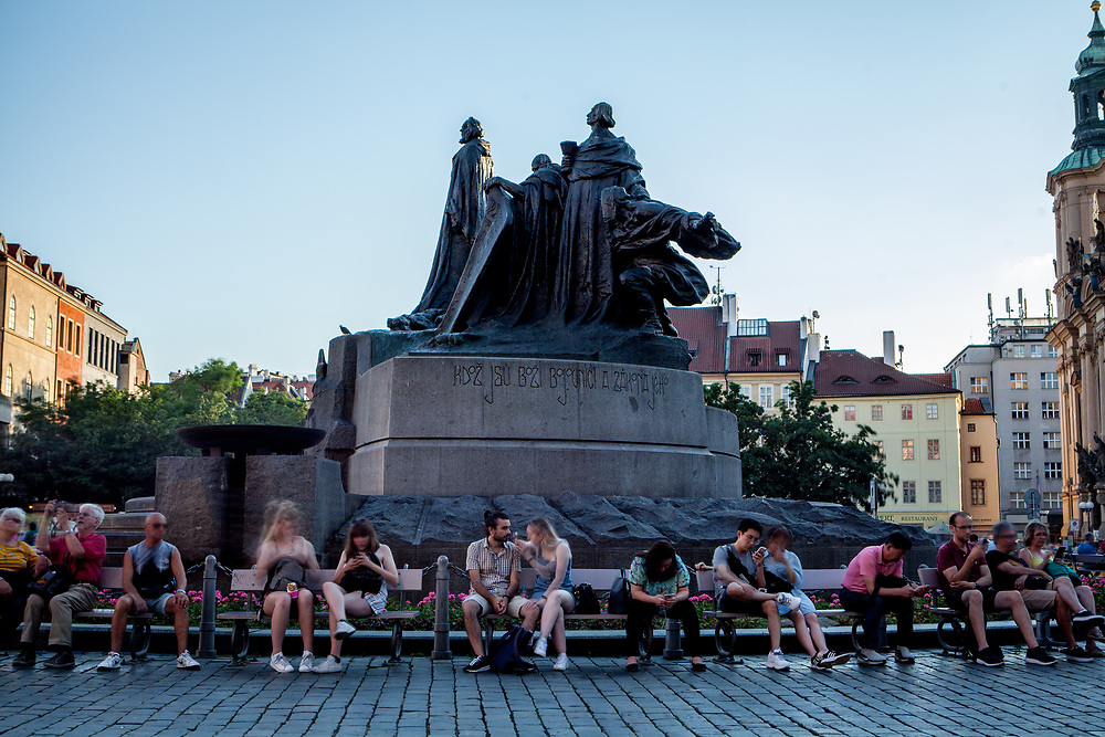 Visitors sitting in-front of the Jan Hus memorial using their mobile phones at Old Town Square.