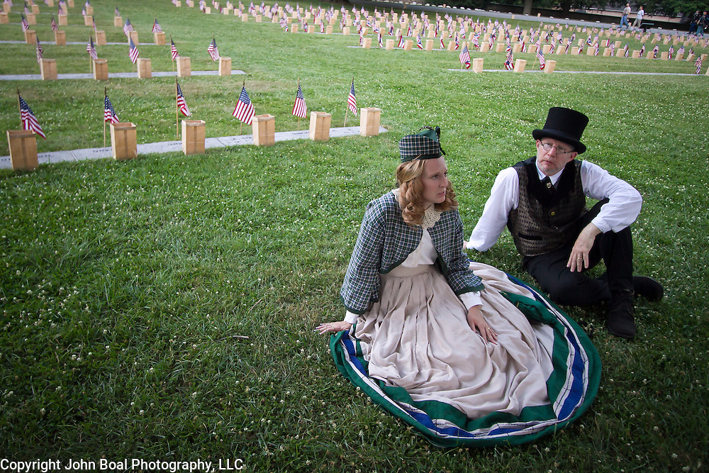 "Civilian reenactors, Lisa and Tom Donnelly take a break in the shade before lighting luminaria at the Soldiers National Cemetery, during the Sesquicentennial Anniversary of the Battle of Gettysburg, Pennsylvania on Sunday, June 30, 2013.   Following ""A New Birth of Freedom"" program at Meade's Headquarters, a procession by candlelight was led to the cemetery. John Boal photography"