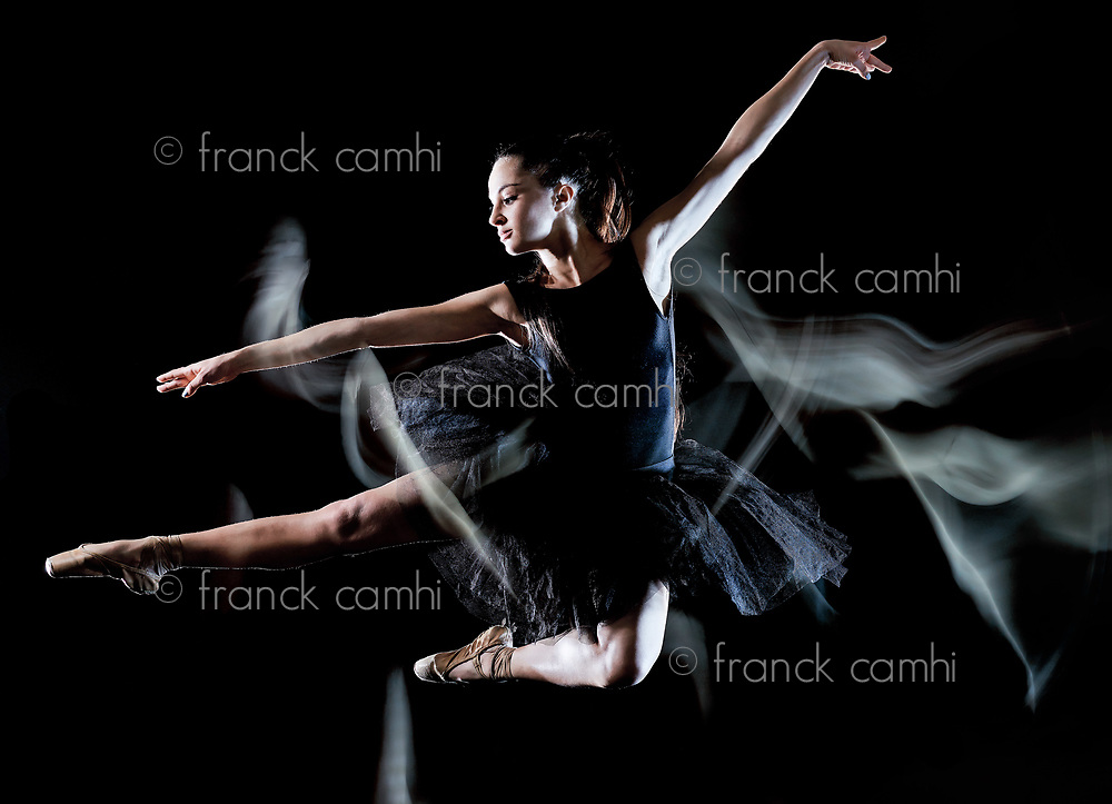 one caucasian young woman ballerina dancer dancing isolated on black background with  light painting motion blur speed effect