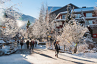 Whistler Village sparkles on a snowy winter day, and the mountain rises steeply behind.