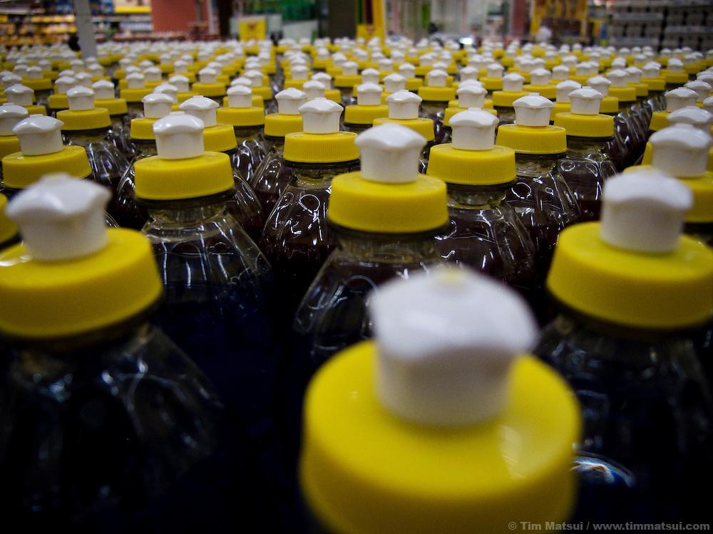 A display of liquid detergent bottles in a supermarket.