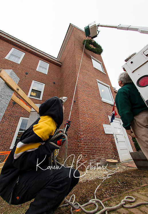 Belknap Mill President Peter Ellis (right) watches as Jake Hutchins and Matt Giuffrida of Hutchins Electric hoist a wreath donated by the Opechee Garden Club to the Belknap Mill Wednesday afternoon.   (Karen Bobotas/for the Laconia Daily Sun)