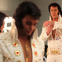 Elvis Tribute Artist Mark Anthony, from Australia, puts on his jewelry as he and the other Tribute Artist get ready backstage at the BancorpSouth Arena before performing in round one of the Ultimate Elvis Tribute Artist Competition Friday morning.
