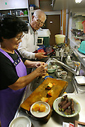 "(MODEL RELEASED) Keiko prepares a meal with her husband Takeo Matsuda in the kitchen of their home. (Supporting image from the project Hungry Planet: What the World Eats.) The Matsuda family of Yomitan Village, Okinawa, is one of the thirty families featured, with a weeks' worth of food, in the book Hungry Planet: What the World Eats. Hara hachi bu: ""eat only until 80 percent full,"" say older Okinawans. The island has been the focus in recent years of researchers trying to discover why a disproportionately large number of Okinawans are living to age 100 or more."