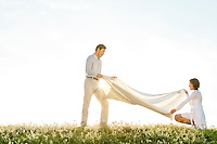 Side view of woman and man spreading picnic blanket on grass during sunny day