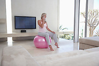 Mature woman sitting on exercise ball in living room talking on phone