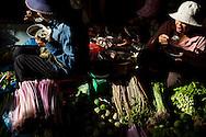 Vendors in Psar Chaa market in Siem Reap, Cambodia eat breakfast in between customers.