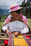 Quechua woman weaving cloth in village of Misminay, Sacred Valley, Peru.