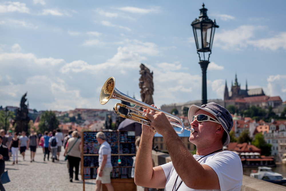 "The ""Kalbo Bridge Band"" performing for natives, tourists and visitors on a crowded Charles Bridge."