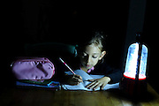 First grade girl of six is doing homework to the light of a rechargeable emergency lamp during a power outage