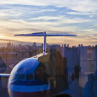 Airport travellers are reflected in the windows overlooking the runways of New York's LaGuardia airport, with the New York skyline at sunset in the background.