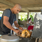 NOVEMBER 23 - TOA ALTA, PUERTO RICO - <br /> Angel Joel Alvarez, 34, cooks a turkey using a gas BBQ grill in his mother in law's garage in the Comunidad Las Acerolas. The house has been without power since Hurricane Maria and it's sheltering several family members.<br /> (Photo by Angel Valentin/FREELANCE)