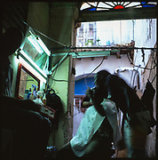 Latino man getting a haircut at Cuban barber, Havana, Cuba