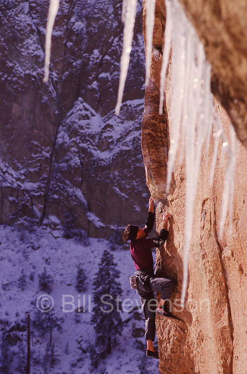 A photo of a man rock climbing in winter at Smith Rock state park in Oregon.