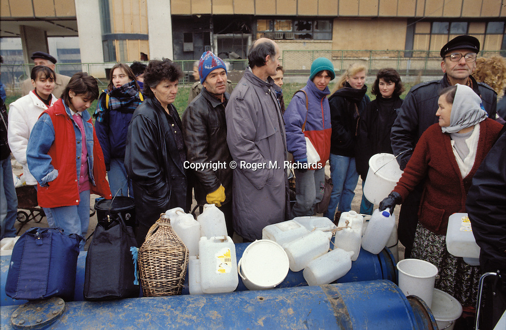 Sarajevans line up for water during the Bosnian Serb siege of Sarajevo, Bosnia and Herzegovina, December 1992. With water supplies and electricity controlled by the Serbs, Sarajevo's citizens were forced to join queues to fill their containers, and were frequent targets of Serb gunners in the hills around the city. Almost 2,000 children, and over 10,000 people in total were killed in Sarajevo during the 3-1/2 year siege. (Photo by Roger Richards)