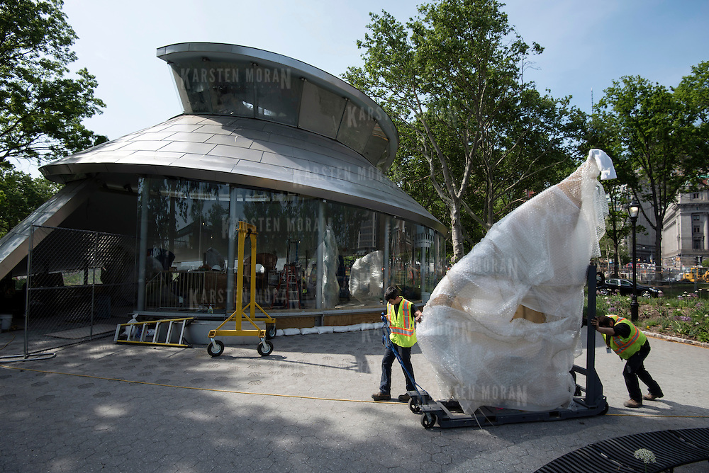 "May 26, 2015 - New York, NY : From left, Cedric Revest and Pascal Boudreau of Show Canada Inc., push a fish wrapped in bubble wrap toward the under-construction Seaglass Carousel on Tuesday afternoon. Four fiberglass fish were delivered to Seaglass Carousel in large crates, in Battery Park on Tuesday morning, May 26. A project of The Battery Conservancy, the Seaglass Carousel, which is set to open in mid-July, is a creation of WXY Architecture and George Tsypin Opera Factory. The carousel will feature thirty fiberglass fish ranging in height from 13'7"" to 3'9"". CREDIT: Karsten Moran for The New York Times"