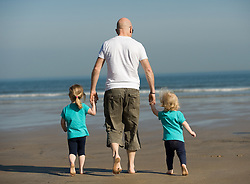 © Licensed to London News Pictures. 28/03/2012..Saltburn, England..As temperatures rise this week the beach at Saltburn in Cleveland attracts the visitors as they enjoy the warm weather. Katie Cuthbert, 3 at left and her sister Hannah, 18 months from Stockton walk to the waters edge with their dad...Photo credit : Ian Forsyth/LNP