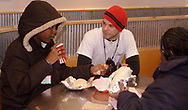 Joe Melendrez (center) talks to Chayilla Polite (left) and Joyce Polite (right) at a burrito party for the homeless hosted by U.D. Religious Studies student Joe Melendrez at Chipotle's on Brown Street in Dayton.