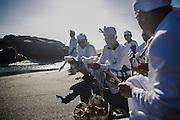 BALI, INDONESIA; MARCH 18, 2015: Balinese Hindu devotees deliver offering to the sea during Melasti, a cleansing ritual before entering Silent Day in Seseh Beach, Bali, Indonesia on Wednesday, March 18, 2015.