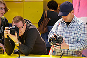 Photokina 2010, World's biggest bi-annual photo fair. Visitors handling DSLRs at the Nikon stand.